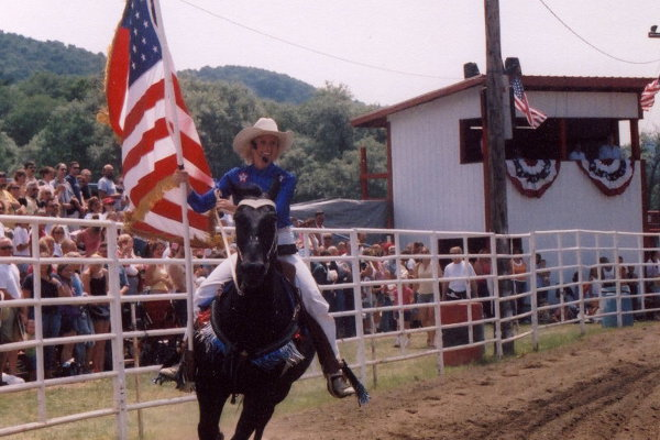 Tammy and the USA flag on horseback at the rodeo